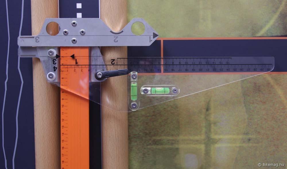 A mind a négy méret beállítását lehetővé tevő mérővonalzó nyugalmi állapotban. Felül az univerzális láb, mely a mérés során a bringa valamely alkatrészéhez illesztve a fix pontot adja. A számok az egyes mérések esetén használatos illesztési pontokat mutatják. Alul a mozgatható fej, rajta a megfelelő méréshez tartozó számozott skála. A mérendő paraméterekhez tartozó illesztési pontok és skálák számozása az elvégzendő méretbeállítások sorrendjét követi. A narancssárga beosztással rendelkező sínen mozog a fej