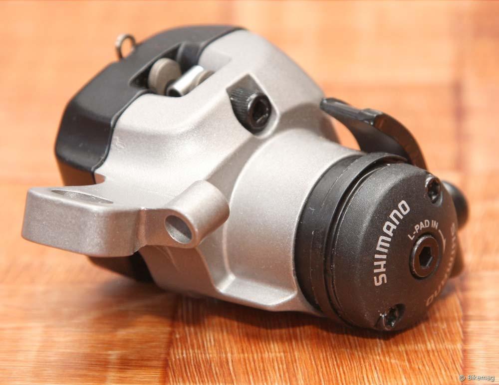 A Shimano jobbik bowdenes féke. Több mint 100 grammal több anyag van benne mint pl. az XT dugattyúban, de kell is, részben a túlmelegedés elkerülésére, részben pedig a minél nagyobb fékmerevség érdekében. A tömege 230 g