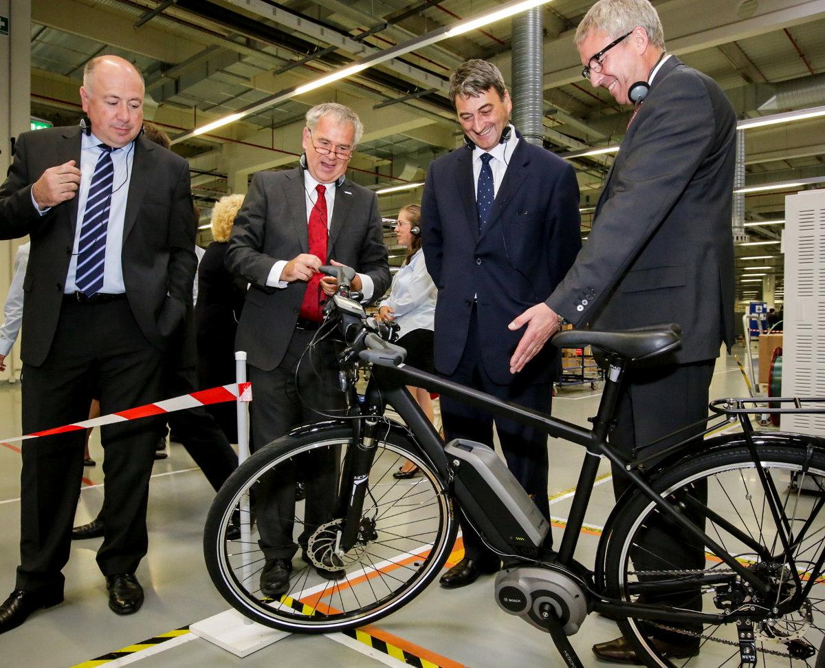 Az illusztris vendégek is megtekintették az e-kerékpárok motoregység-gyártását, a gyárigazgató az államtitár polgásmester úrnak szemlélteti a technológia lényegét...