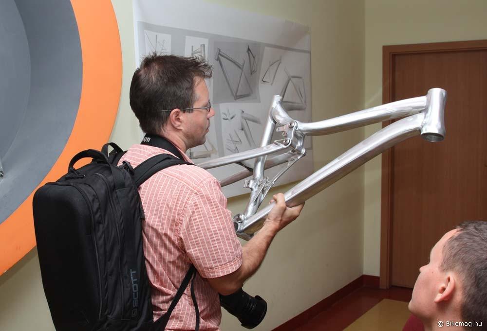 András éppen az XC/Maraton össztelós váz prototípusát vizslatja, a háttérben a falon koncepcióvázlatok figyelnek