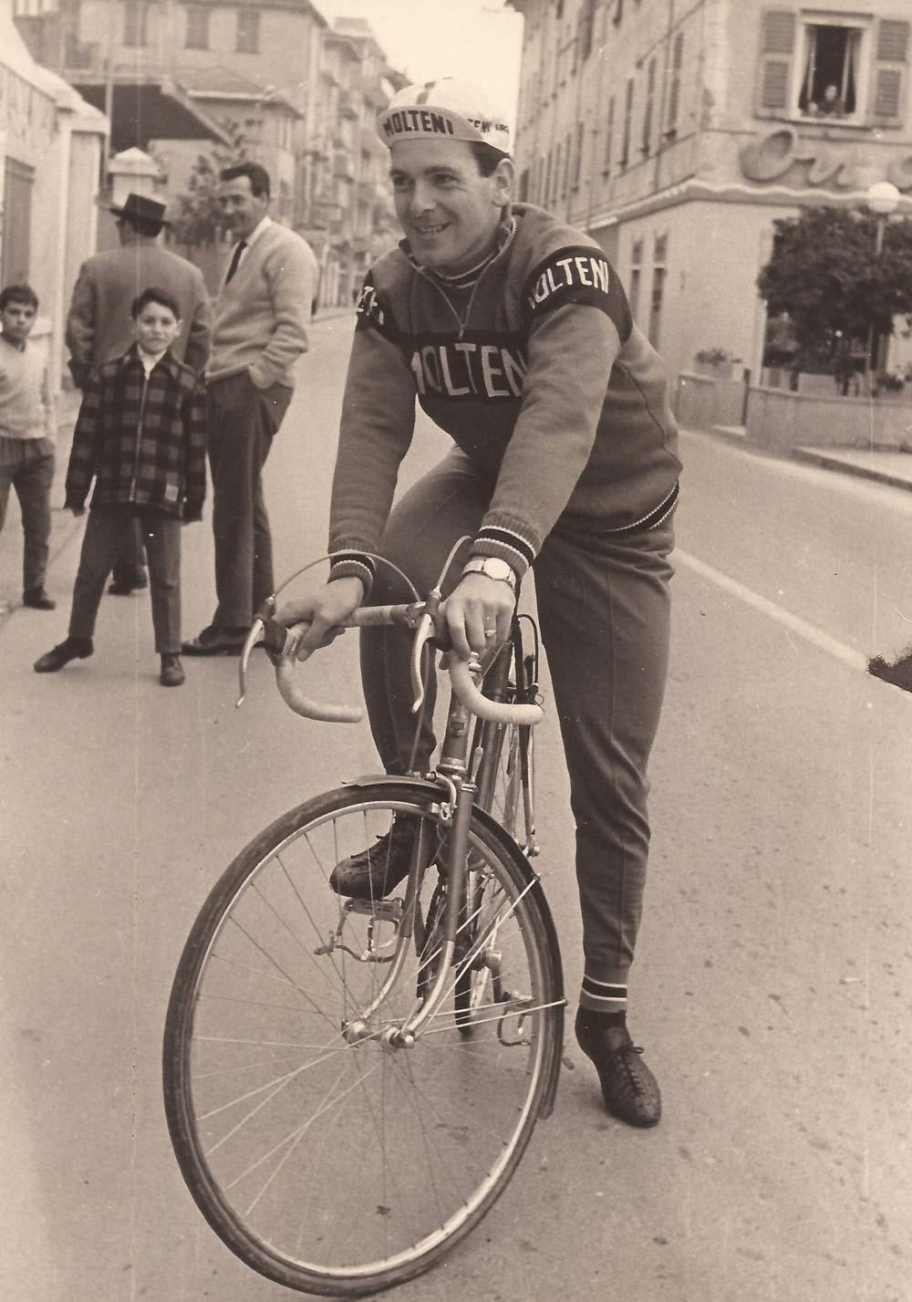 Trento, utcakép. Profi edzésre indul. Egész pontosan 1961-ben járunk, ez már a Merckx-ről is ismert aranybarna ancúg, a fekete sávban Molteni felirattal. A mackóalj szárának közepére varrt borda, biztos a légellenállás miatt… Széles passzé és a sárvédő is átfér végre a villa alatt. A hatvanas évek elején a profi kerékpárosnak lenni is csak egy szakma volt a többi között
