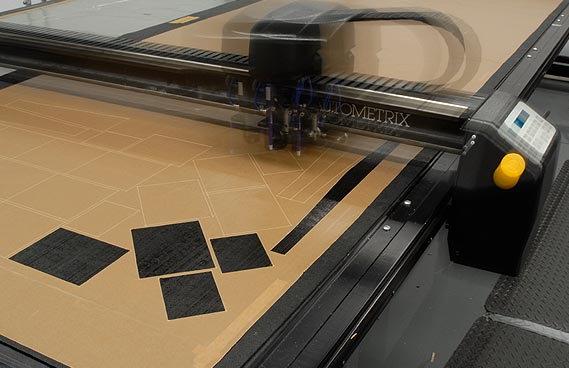 Az előre laminált karbonszövetet CNC géppel tizedmilliméter pontosággal szabják le...