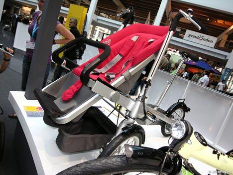 """Taga - """"Babakocsicikli"""". A termék egy új fogalom: ha az ülést a babaülő rész alá becsukjuk egy """"normál"""" babakocsi, míg kihajtott helyzetben a gyermek mögött tekerhetünk."""