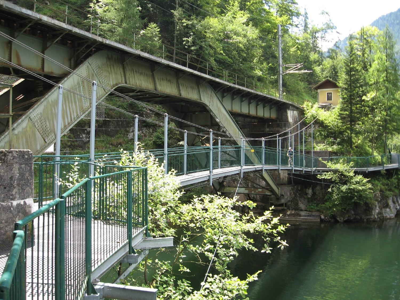 A Halstatti tó keleti partján kerékpárút fut végig, ahol más megoldás nem akadt, ott a sziklafalra függesztett acéljárdán fut. A képen kis függőhíd ível át a vasúti híd tövében Halstattal szemben.